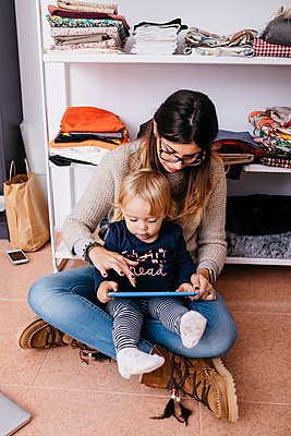 Mother and little daughter sitting on the floor at home using tablet - p300m2059008 by Josep Rovirosa