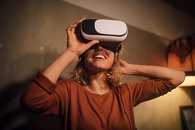 Laughing young woman putting on Virtual Reality Glasses at home - p300m2119815 by Christian Gohdes