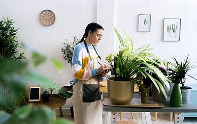 Young woman working in a gardening laboratory or plant shop - p300m2275351 von Giorgio Fochesato