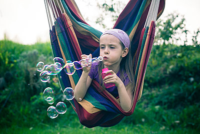 Portrait of little girl blowing soap bubbles - p300m926622f by Sandra Roesch