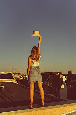 Junge Frau steht mit Hut auf Hausdach - p432m2260424 von mia takahara