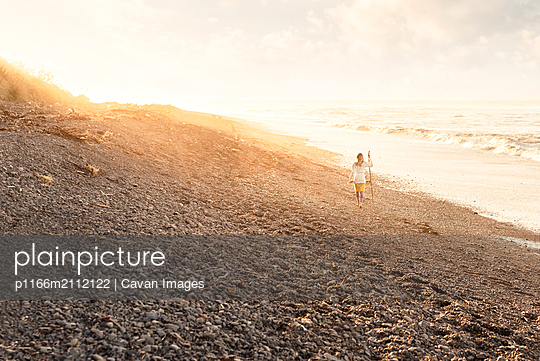 Girl holding walking stick on a rocky beach at dusk in New Zealand - p1166m2112122 by Cavan Images