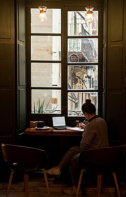 Young student is studying in a coffee shop with her laptop - p1166m2153669 by Cavan Images