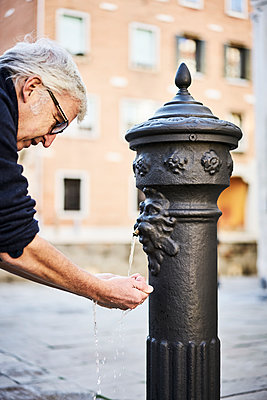 Man refreshing at a well - p1312m2054993 by Axel Killian