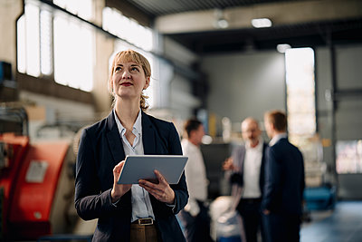 Portrait of a confident businesswoman with tablet in a factory with colleagues in backgound - p300m2171093 by Kniel Synnatzschke