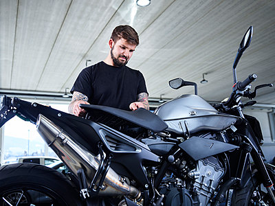 Young male repairman installing motorcycle part at garage - p300m2281552 by Christian Vorhofer