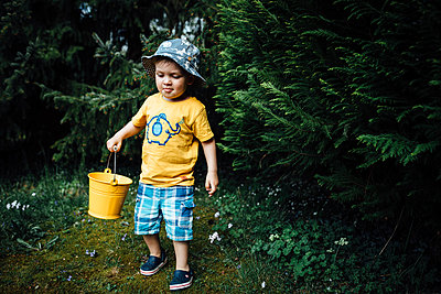 Little boy finding Easter eggs in Spring on an Egg hunt - p1166m2090683 by Cavan Images