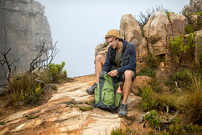 Young man on a hiking trip high in the mountains - p1355m1574136 by Tomasrodriguez