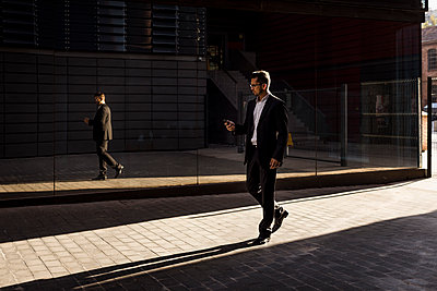 Businessman walking in the city checking cell phone - p300m2070062 by Mauro Grigollo