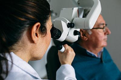 ENT physician examining ear of a senior man - p300m2179841 by Andrés Benitez