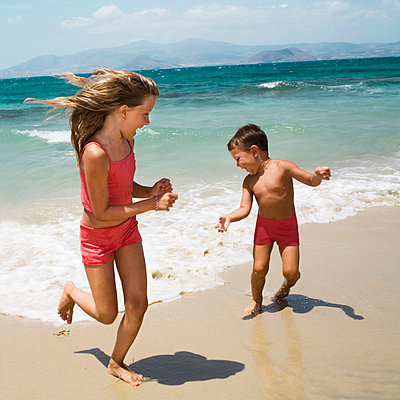 A brother and sister running on a beach - p31223341 by Susanne Walstrom