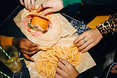 High angle view of friends eating burger and french fries at table in cafe - p426m2194694 by Maskot