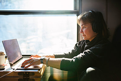 Businesswoman using laptop while sitting by window in train - p426m2279912 by Maskot