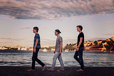 Profile shot of young men walking in a row on pier - p426m844739f by Maskot