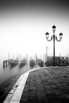 Black and white gondolas and lamp in the mist, St. Mark's Square, with Grand Canal in the background, Venice, UNESCO World Heritage Site, Veneto, Italy, Europe - p871m1583773 by Ed Hasler
