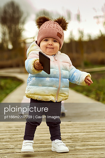 A 1 year old baby girl is with a pink motorcycle outside - p1166m2207759 by Cavan Images