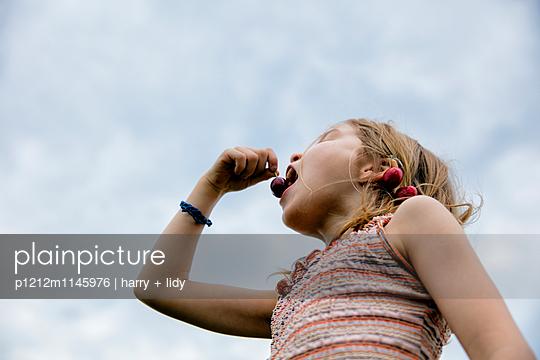 Mädchen isst Kirschen vor Himmel - p1212m1145976 von harry + lidy