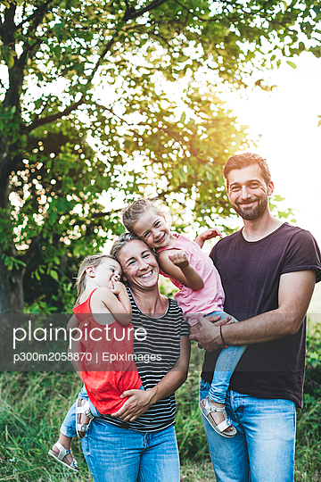 Portrait of happy family with two daughters standing in nature - p300m2058870 by Epiximages