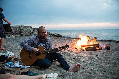 Mann spielt Gitarre am Lagerfeuer am Strand - p1142m1362259 von Runar Lind