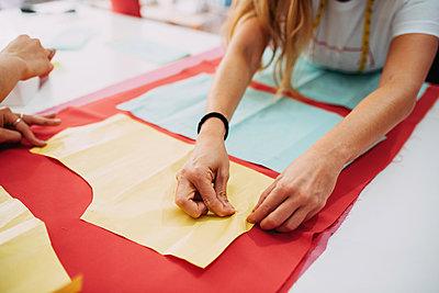 Fashion designer preparing fabric to cut - p1166m2131013 by Cavan Images