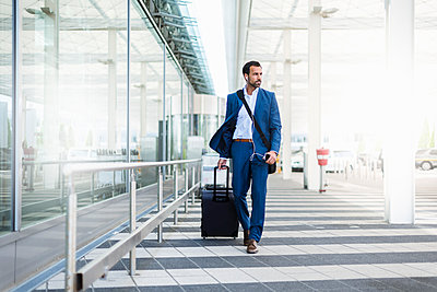 Businessman with trolley and smartphone at airport - p300m1587863 von Daniel Ingold