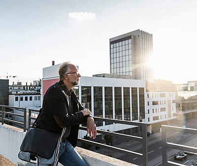 Mature man standing on rooftop, leaning on railing - p300m2023961 von Uwe Umstätter