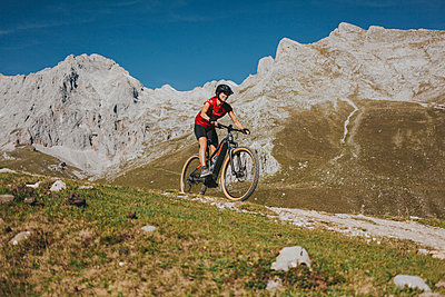 Female cyclist riding mountain bike on trail at Picos de Europa National Park, Cantabria, Spain - p300m2240188 by David Molina Grande