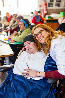 Happy female caregiver with disabled man in rehabilitation center - p300m2243794 by DREAMSTOCK1982