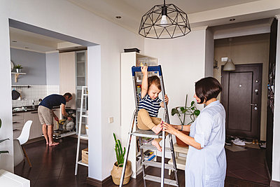 Mother playing with son sitting on ladder while father working in kitchen at home - p300m2276683 by Katharina und Ekaterina