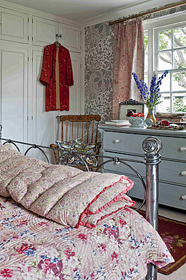 Painted chest of drawers and quilts on metal framed bed in London home - p349m790959 by Polly Eltes