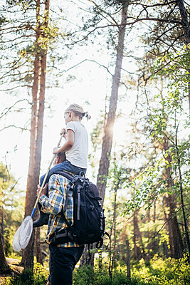 Low angle view of father carrying daughter on shoulder in forest - p426m2213312 by Maskot