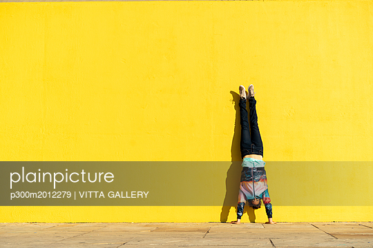 Acrobat doing handstand in front of a yellow wall - p300m2012279 von VITTA GALLERY