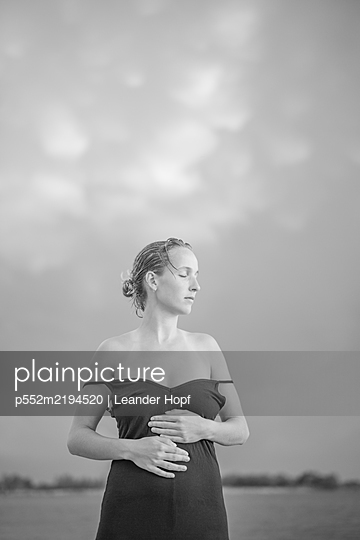 Young woman in sexy strap dress - p552m2194520 by Leander Hopf