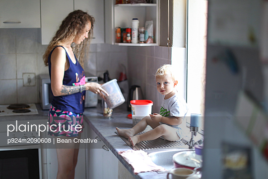 Mother and baby son preparing breakfast in kitchen - p924m2090608 by Bean Creative