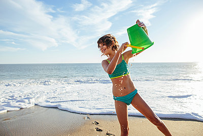 Smiling girl playing with bucket at beach against sky - p1166m1182985 by Cavan Images