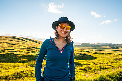 woman wearing sunglasses and hat enjoying a sunny day in Iceland - p1166m2261812 by Cavan Images