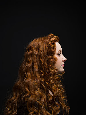 Profile portrait serious woman with long curly red hair against black background - p1192m1403560 by Hero Images