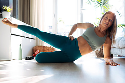 Young woman lying on side while exercising at home - p300m2255999 by Josep Suria