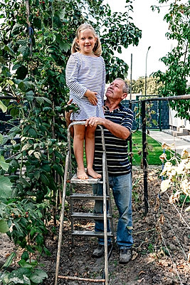 Granddaughter standing on ladder by grandfather in backyard - p300m2276124 by Oxana Guryanova
