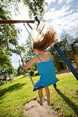 Germany, Coburg, teenage girl on a swing in the park - p300m981171f by Val Thoermer