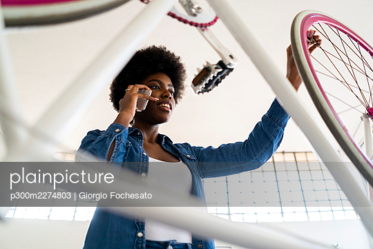 Afro woman using mobile phone while repairing bicycle - p300m2274803 by Giorgio Fochesato