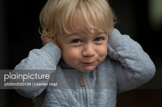 Little boy hold their hands over their ears - p552m2020158 by Leander Hopf