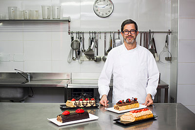 Cheerful chef in kitchen with rolled cakes - p1166m2130396 by Cavan Images