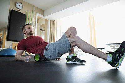 Man stretching back on roller in physiology clinic gym - p1192m1447350 by Hero Images
