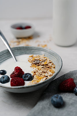 Bowl of granola with yogurt, blueberries and raspberries - p300m2166532 by Juanma Hache
