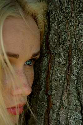 Young woman leaning against tree trunk, looking away sadly - p675m922865 by Frederic Cirou