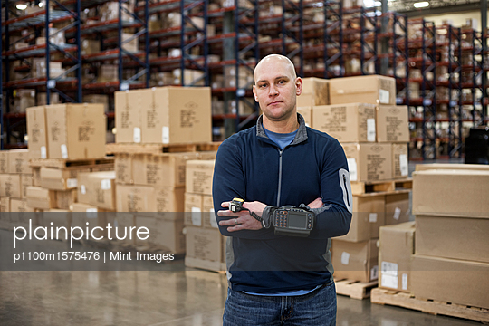 Portrait of a Caucasian warehouse worker in a large distribution warehouse, showing products stored in cardboard boxes. - p1100m1575476 by Mint Images