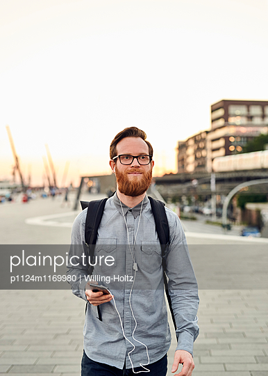 Mann mit Smartphone auf dem Arbeitsweg - p1124m1169980 von Willing-Holtz