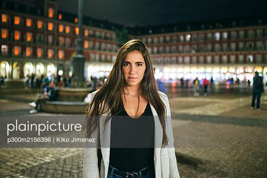 Portrait of a woman standing on Plaza Mayor at night, Madrid, Spain - p300m2156396 by Kiko Jimenez