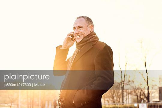 Mann telefoniert im Gegenlicht - p890m1217303 von Mielek